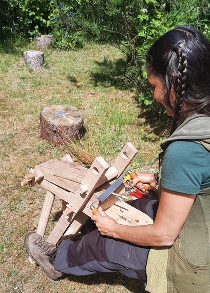 Women demonstrating green woodworking skills using a 'shave horse'.